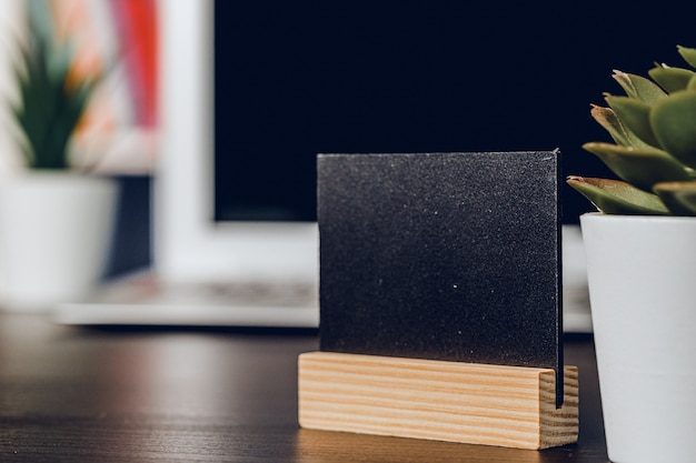 Little black tag on wooden stand on office working table. copy space for your text