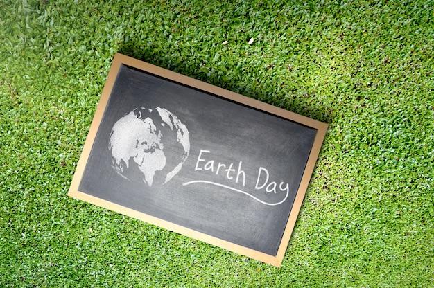 草の上の地球の日のメッセージと小さな黒板