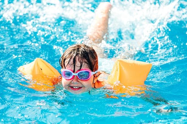 미소하고 소매와 수영 고글을 착용 수영장에서 수영하는 작은 blackhaired 소녀