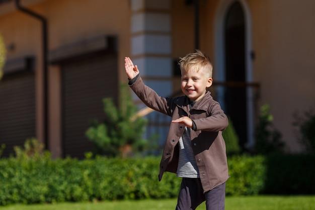庭でロボットをやっている小さな金髪の少年
