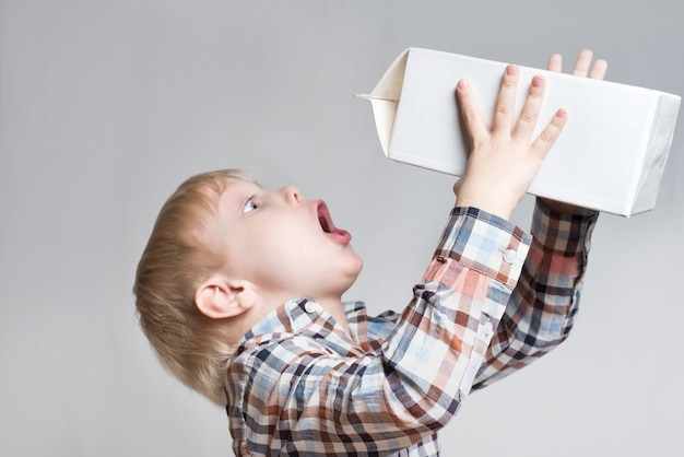 Little blond boy drinks from a large white package.