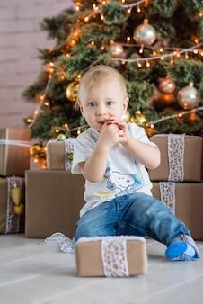 Маленький белокурый мальчик ест пряничный человечек у елки дома.