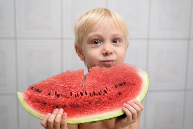 小さな金髪の少年はスイカの大きな塊を食べます。夏のコンセプト。ホームインテリア