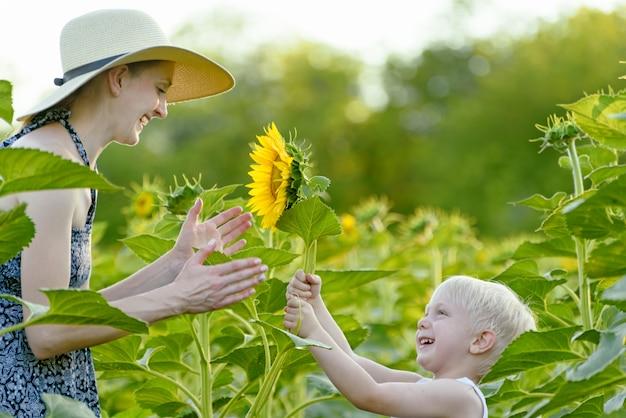 Little blond boy gives his mother a sunflower flower