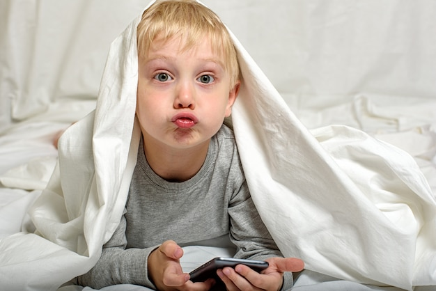 Little blond boy grimaces with a smartphone in his hands