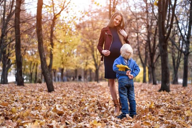 Маленький белокурый мальчик спрятался за желтым листом. хочет подарить маме. осенний парк на заднем плане