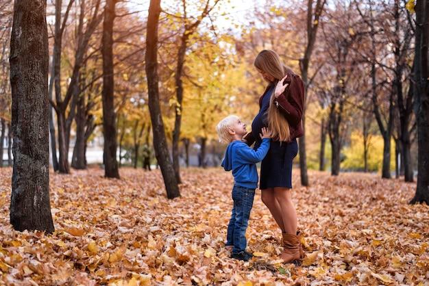 Маленький белокурый мальчик обнимает живот беременной мамы. осенний парк на заднем плане