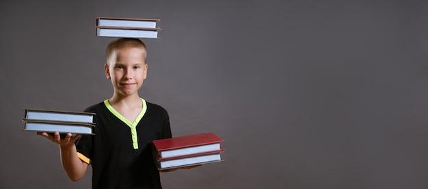 黒のtシャツを着た小さな金髪の少年は、あなたの手と頭にたくさんの本を持っています。子供は灰色の背景で隔離されたカメラを見ています。