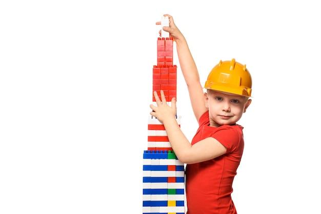 Маленький белокурый мальчик в строительном шлеме и красной рубашке стоит возле башни, построенной из деталей конструктора