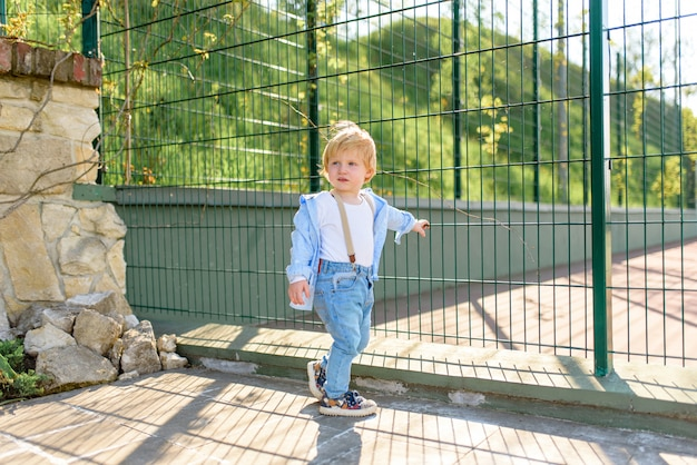 A little blond boy is standing near the fence