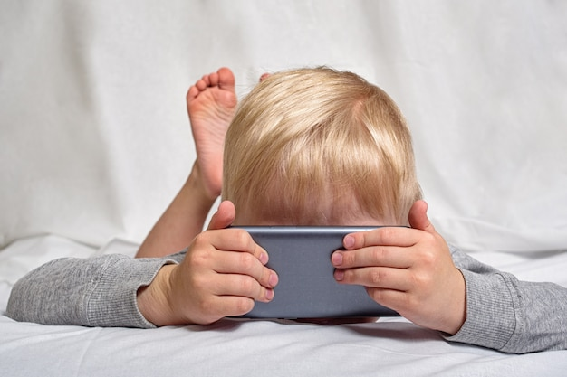Little blond boy looking something his nose buried in a smartphone, lying in bed. gadget leisure