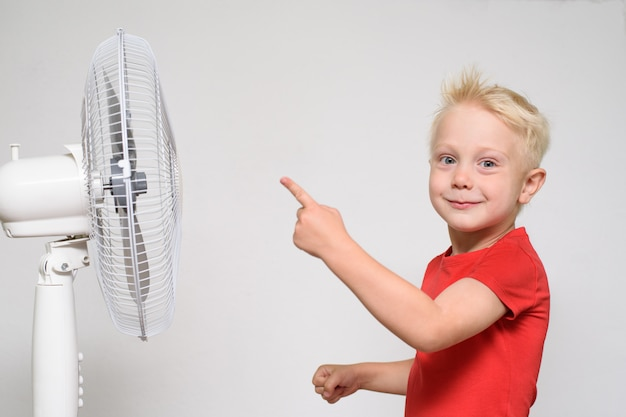Little blond boy in a red t-shirt points a finger at the fan. summer concept