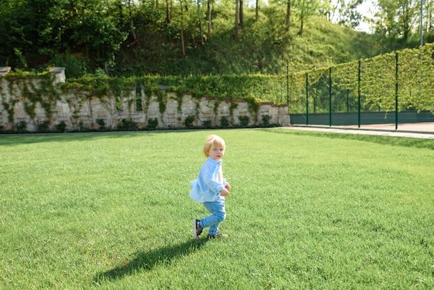 Little blond boy runs on green grass