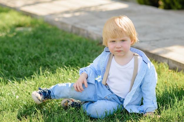 Маленький белокурый мальчик сидит на зеленой траве