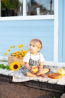 Little blond boy sitting on a wooden porch at home and eats an apple on an autumn day. child plays in the yard in the fall.