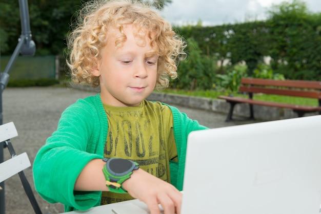 Little blond boy using a laptop, outdoors