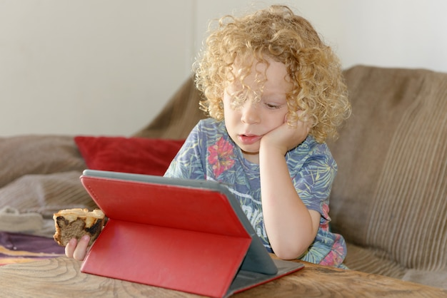 Little blond boy using tablet computer