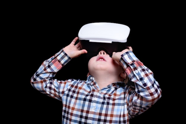 Little blond boy with glasses of virtual reality looks up. plaid shirt