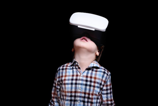 Little blond boy with glasses of virtual reality looks up