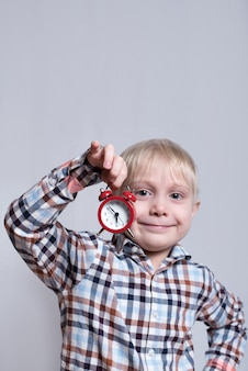 Little blond boy with a red alarm clock in his hands. morning concept