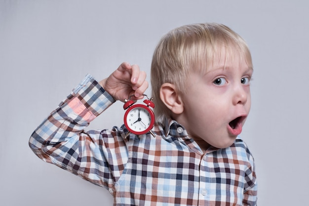 Little blond boy with a red alarm clock in his hands. surprised face. morning concept.