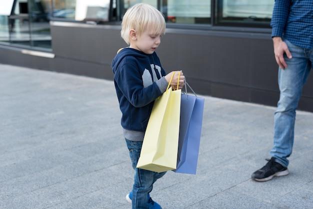 Маленький белокурый мальчик с хозяйственными сумками. семейный шоппинг