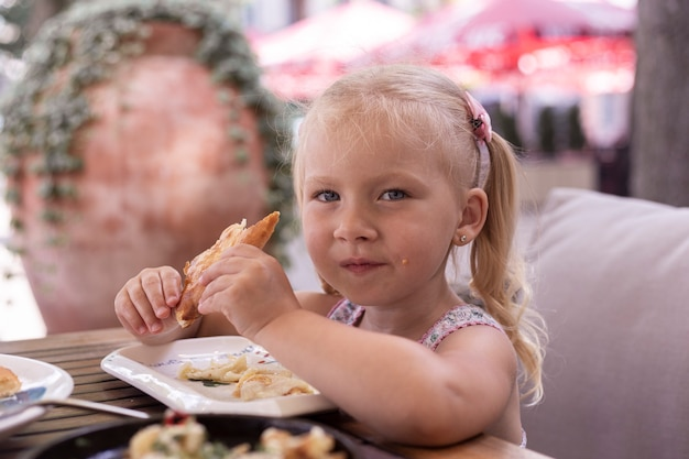 Маленький белокурый ребенок ест в летнем кафе. настоящие люди.