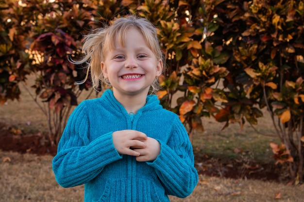 정원에 있는 차가운 스웨터를 입고 카메라를 보며 웃고 있는 금발 소녀