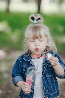 Маленькая блондинка дует с напыщенным и пузыри