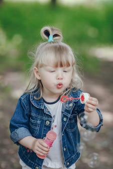 Little blond girl blowing by a pompous and making bubbles