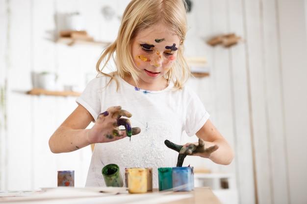 ペイントで彼女の指を深めるブロンド少女。絵に染まったヨーロッパの女性の子供は、顔にペイントスポットが付いた白いtシャツを着ています。子供とアート。