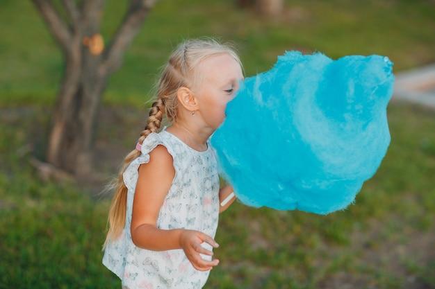 公園で青い綿菓子を食べる小さなブロンドの女の子。