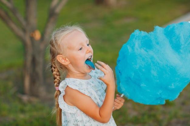 綿菓子を食べている小さなブロンドの女の子は、公園で青い舌を示しています。