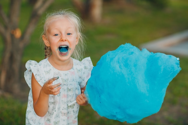 Little blond girl eating cotton candy and shows blue tongue in the park