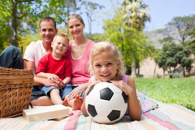 ピクニックでサッカーボールを持っている小さな金髪の女の子