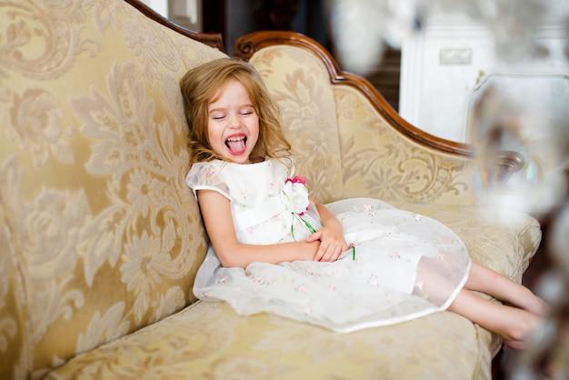 Маленькая белокурая девочка в красочном платье, сидящем на большом диване.