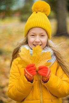 노란 잎이 달린 노란 옷을 입은 금발 소녀, 가을