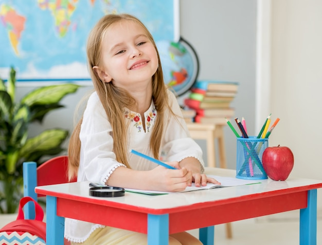 白い机に座って、学校の教室で笑っている小さなブロンドの女の子