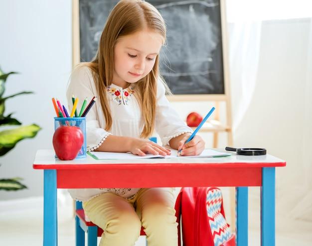 学校の教室で授業を書く小さなブロンドの女の子