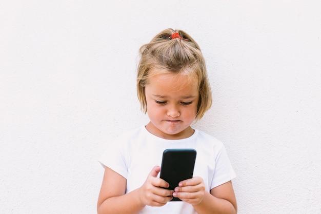 白いtシャツを着て、携帯電話を見て、集中した顔の小さなブロンドの髪の少女