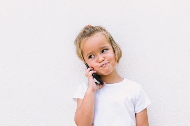 白いtシャツを着て、携帯電話で話している、笑顔で小さなブロンドの髪の少女