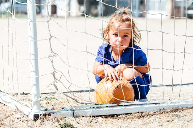 Little blond-haired girl wearing blue soccer uniform in goal with a ball