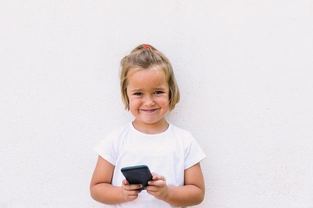 白いtシャツを着て、携帯電話を手に持ってカメラを見ている金髪の少女