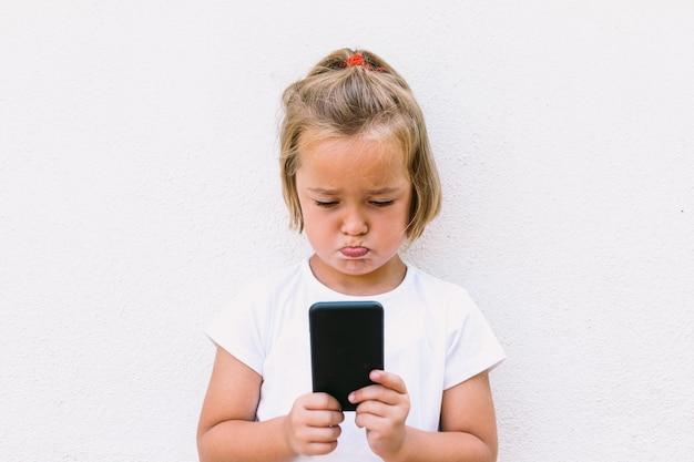白いtシャツを着て、携帯電話を見て、背を向けて、ビデオを見て、怒った顔をした金髪の少女