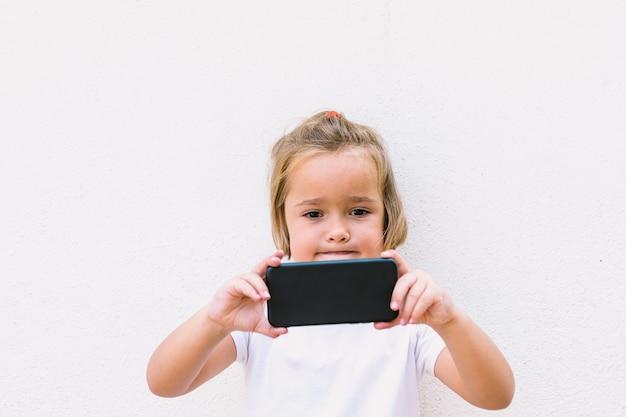 写真を撮りながら、白いtシャツを着て、携帯電話を回して見ている金髪の少女