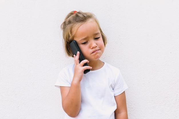 不機嫌そうな顔で、携帯電話で話している白いtシャツを着ている小さなブロンドの髪の少女