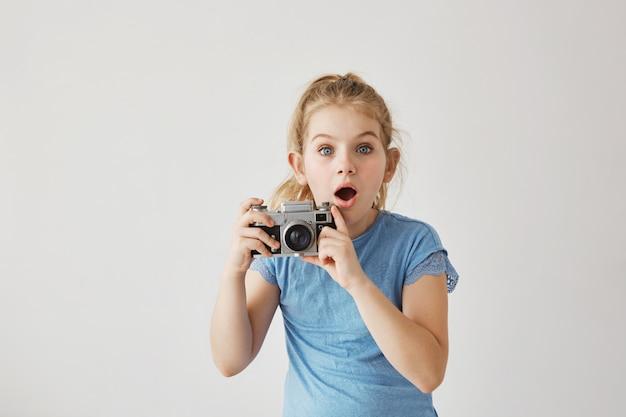 青い目をした金髪の小さなミスは、父親が転んで倒れたときにフィルムカメラで両親の家族写真を撮っていた。見ている子供は、親が怪我をすることを怖がっています。