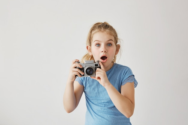 Little blond miss with blue eyes was taking family photo of parents with film camera when dad slipped and fell down. child looking frightened that parent get hurt.