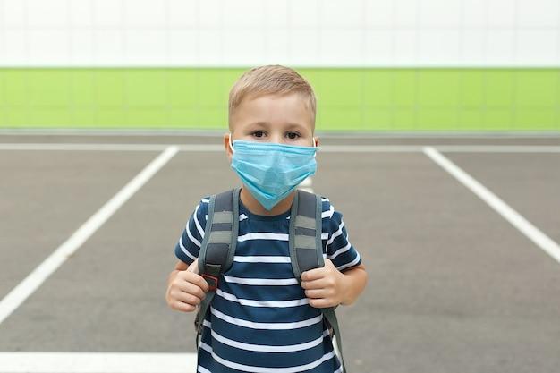 コロナウイルスの発生時にマスクを身に着けている小さな金髪の男子生徒