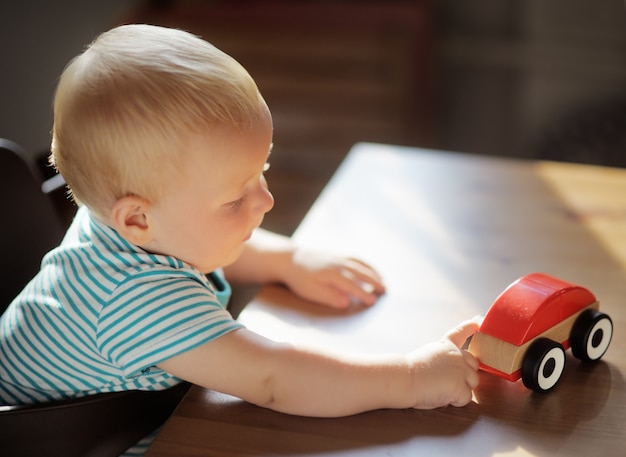 Little blond toddler boy playing with toy car